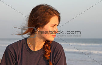 Teenage girl at the windy beach.