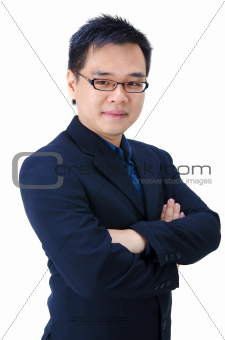 Asian business man standing with arms folded.
