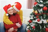 Young man kissing girlfriend near Christmas tree