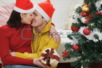 Romantic young couple with gift kissing near Christmas tree