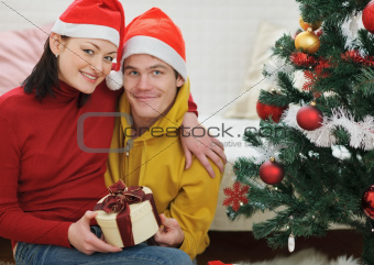 Happy young couple with gift sitting near Christmas tree