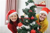 Cheerful young couple looking out from Christmas tree