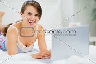 Smiling young woman laying on bed and using laptop