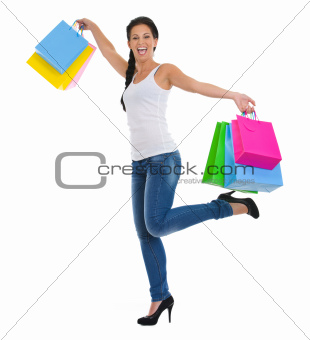 Full length portrait of cheerful girl with shopping bags