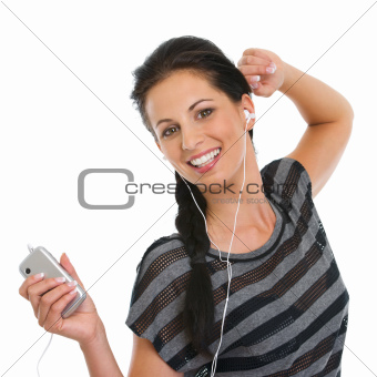 Portrait of happy girl listening music in headphones and dancing