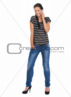 Full length portrait of smiling girl speaking mobile phone