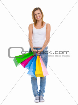 Full length portrait of smiling teenage girl with shopping bags