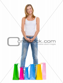 Full length portrait of smiling teenage girl standing among shopping bags
