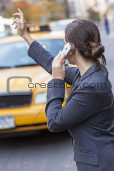 Young Woman on Cell Phone Hailing a Yellow Taxi Cab