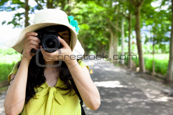 Young traveler taking photo in the green forest