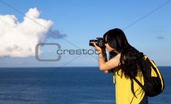 Young woman taking photo with cloud background