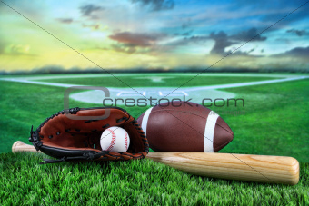 Baseball, bat, and mitt in field at sunset