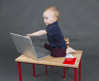 baby with laptop computer in grey background