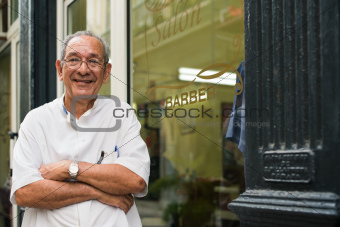 portrait of old barber smiling in hair salon