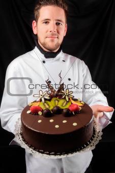 Handsome chef with cake against dark background