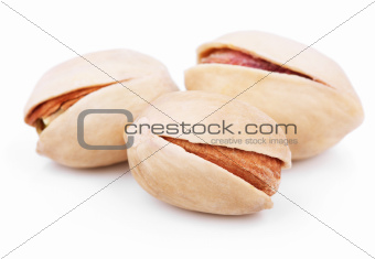 Three pistachio nuts on white