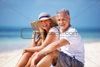 Portrait of happy mature couple enjoying their vacation at beach