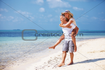 Full length of mature couple enjoying piggy back ride together on beach
