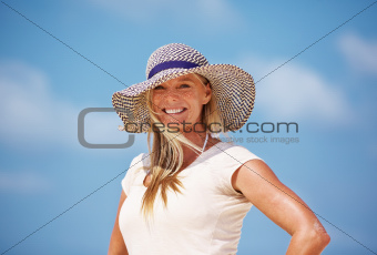 Portrait of attractive mature woman smiling in sun hat outdoors