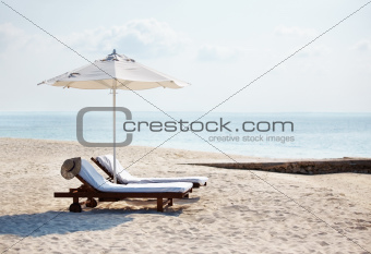 Deck chairs with umbrella and beautiful beach on sunny day