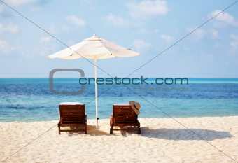 Lounge chairs with umbrella on beach shore