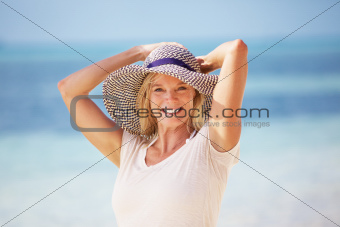 Portrait of beautiful mature woman smiling in sun hat at beach