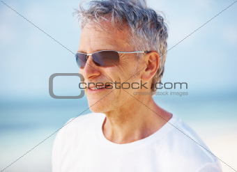 Portrait of stylish mature man in shades smiling outdoors