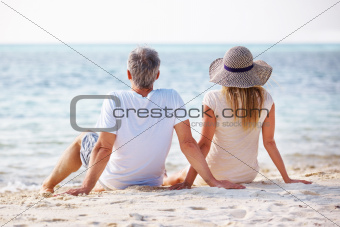 Rear view of relaxed mature couple sitting together on the beach