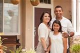 Hispanic Mother, Father and Daughter in Front of Their Home.