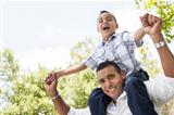 Hispanic Father and Son Having Fun Together Riding on Dad&#39;s Back in the Park.