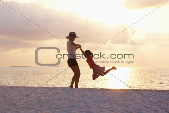 Portrait of joyful mother and daughter having good time on the beach