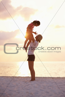 Full length of playful mother with daughter on the beach