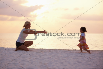Portrait of little daughter running towards mother on the beach