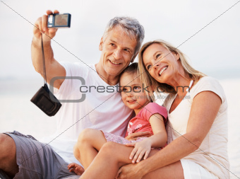 Portrait of happy family taking self portrait with camera