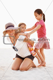Portrait of young mother giving piggyback ride to little kid with sister sibling on the beach
