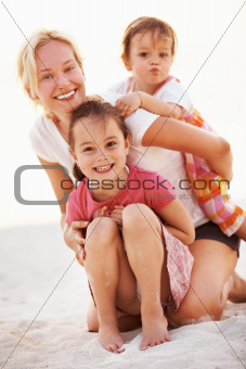 Portrait of happy mother having fun with daughters on the beach