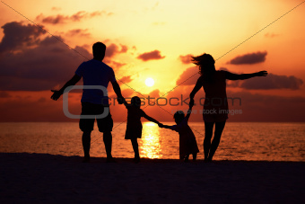 Silhouette of affectionate family enjoying while walking on the beach at sunset