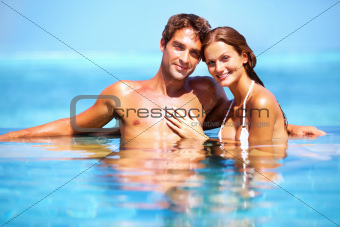 Young attractive couple sitting in a pool