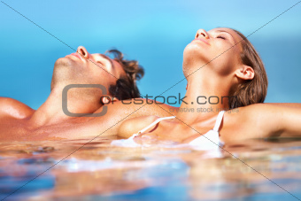 Attractive couple pelaxed and tanning in a pool