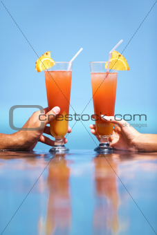 Male and Female hands holding cocktails in the sun