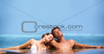 Lovely couple relaxed in a pool with the ocean in the background