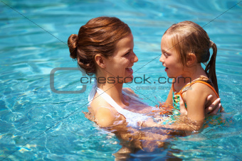 Pretty mother playing with her daughter in the pool