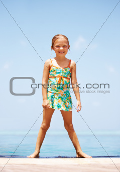 Cute young girl standing on the edge of her pool after a swim