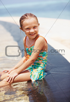 Pretty young girl sitting on the edge of her pool