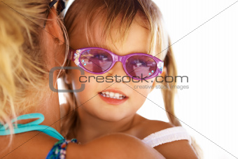 Cute girl with sunglasses on being held by her mother