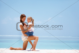 Mother holding her daughter on her knee at the beach