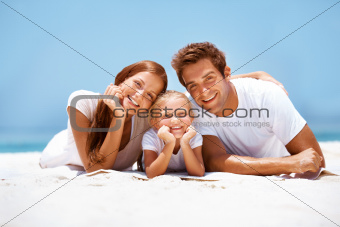 Beautiful young family lying and smiling on the beach
