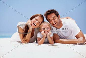 Smiling young family lying on the sand at the beach