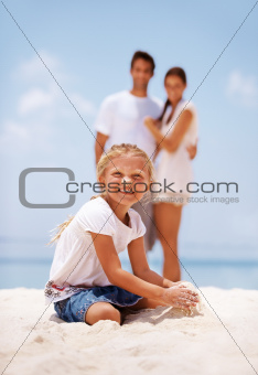 Pretty little blonde girl playing in the sand with her parents in background