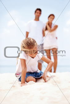 LIttle girl at the beach digging in the sand with  parents behind her